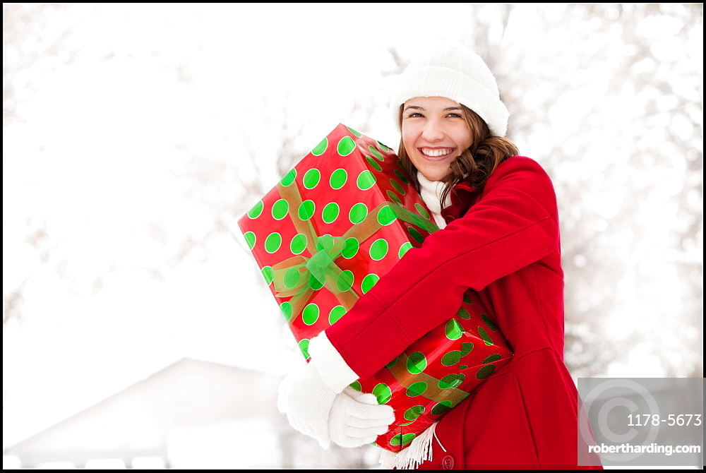 USA, Utah, Lehi, Portrait of young woman hugging Christmas gift outdoors