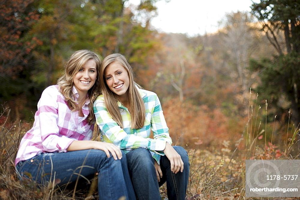 USA, Utah, Sundance, Portrait of two young women sitting on meadow