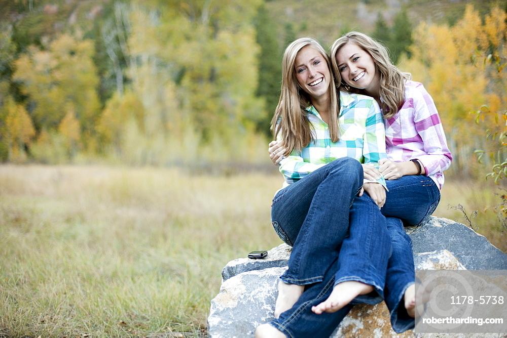 USA, Utah, Sundance, Portrait of two young women sitting on boulder