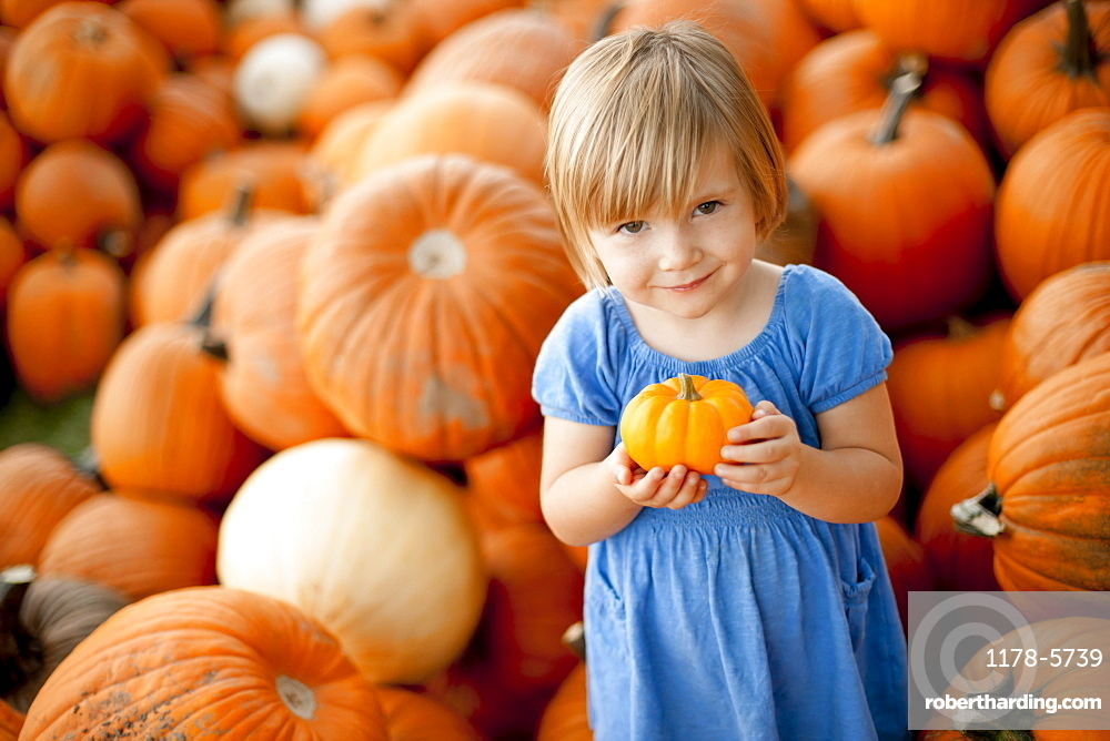USA, Utah, Orem, portrait of girl (2-3) holding pumpkin