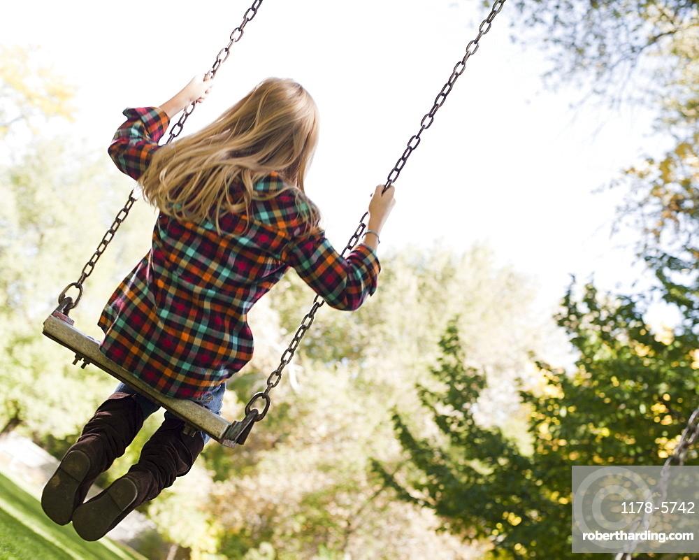 USA, Utah, girl  (6-7) swinging on tree swing