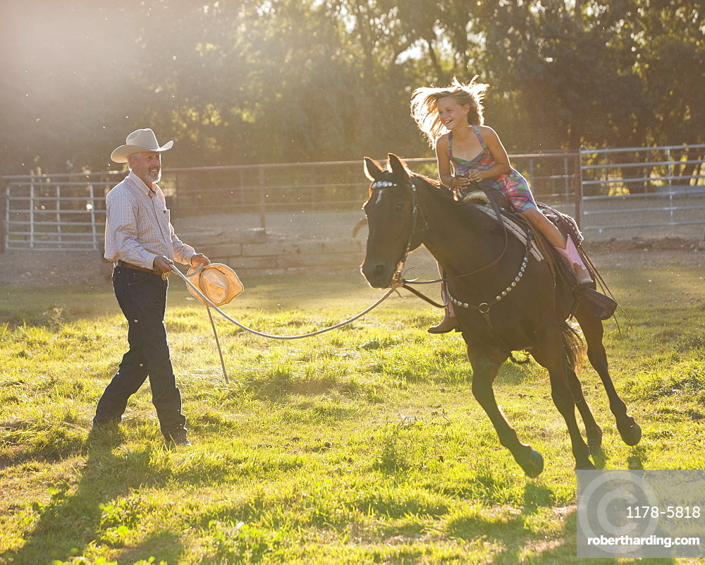 Trainer assisting girl (8-9) riding horse in paddock