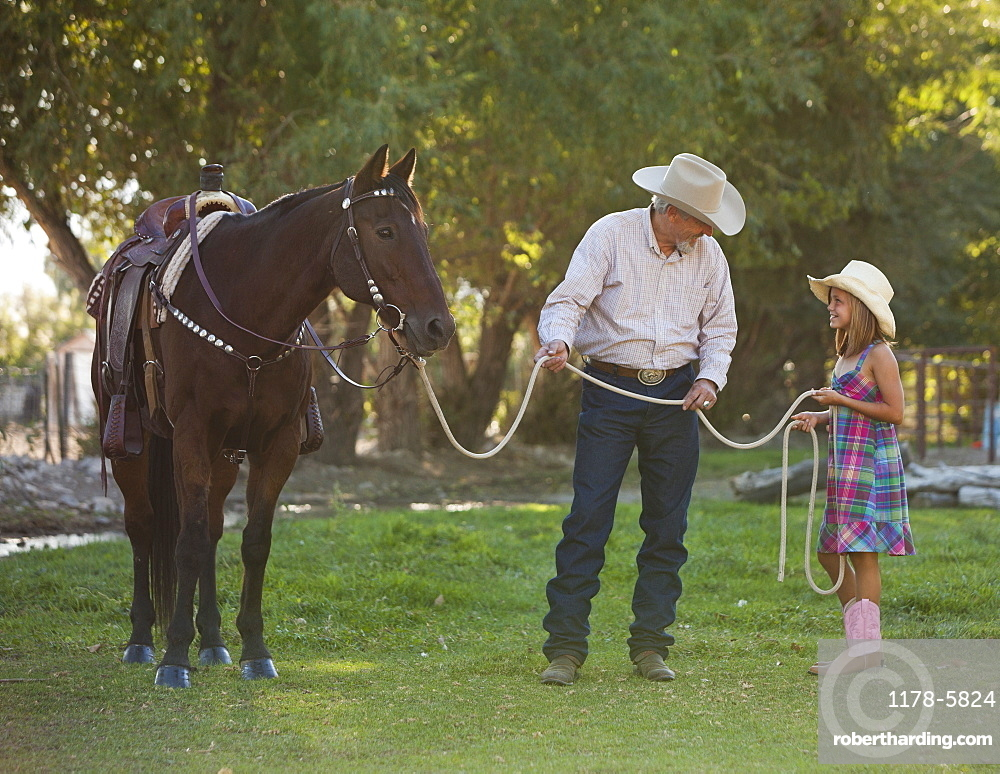Senior man with granddaughter (8-9) training horse in ranch