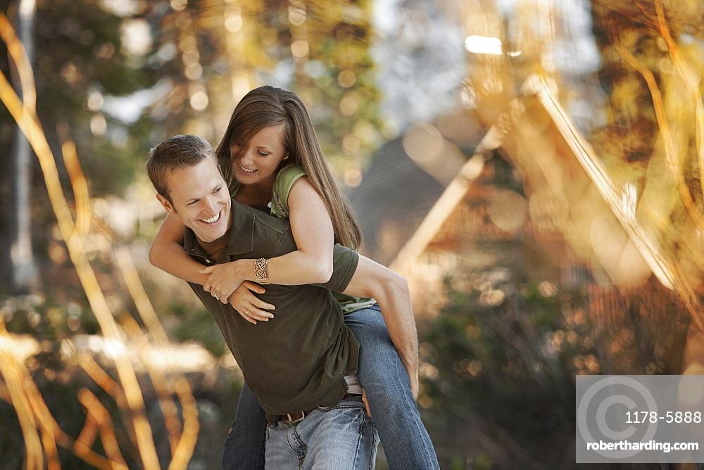 Man giving girlfriend a piggyback ride