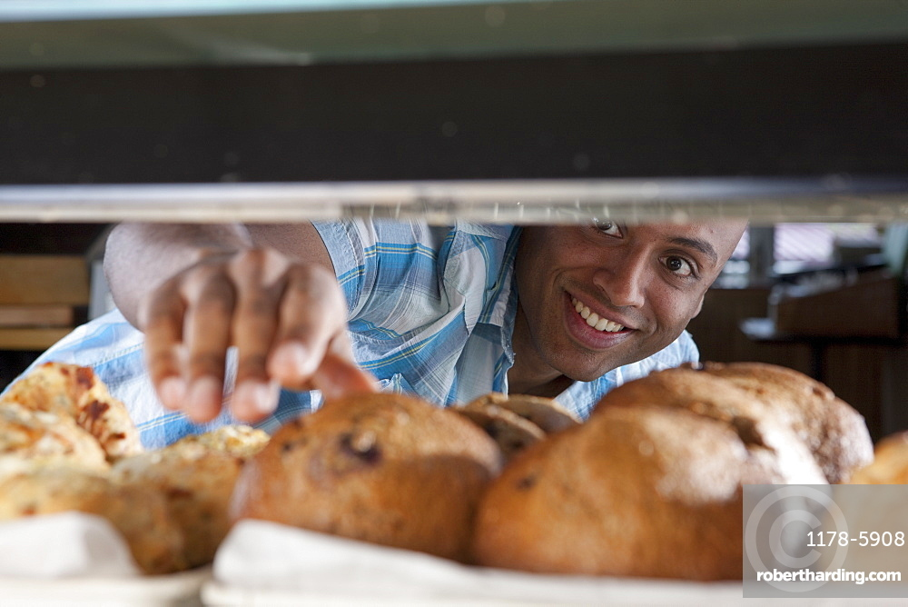 Man reaching for muffin in bakery