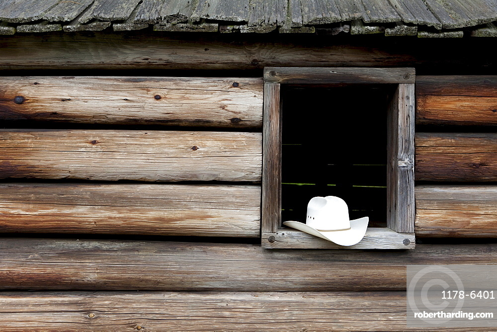 A cowboy hat in the window of a cabin