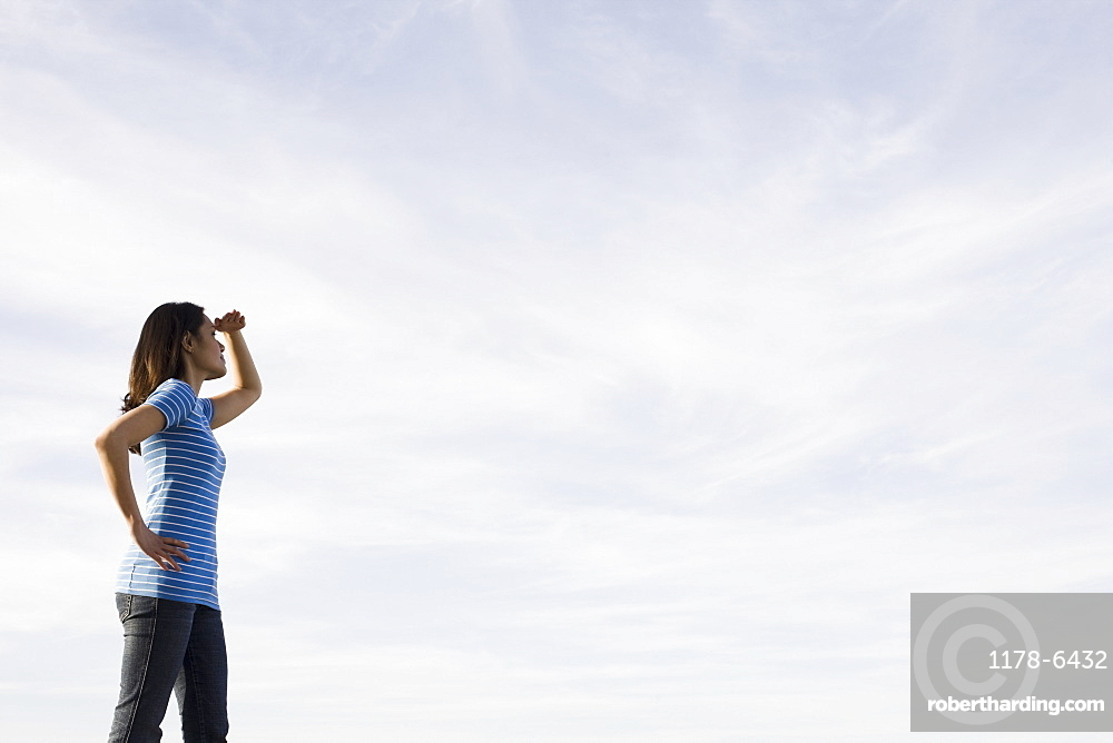 Woman shielding eyes against sky