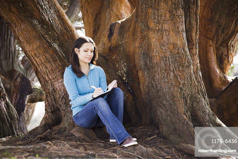 Woman writing diary by tree in park
