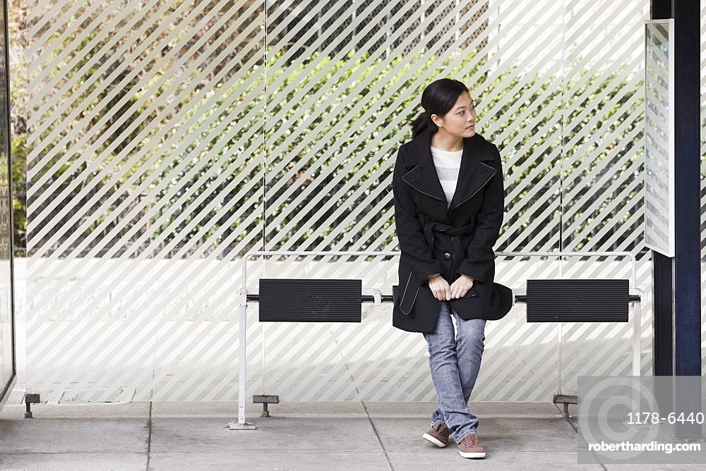 Young woman waiting at bus stop, San Francisco, California, USA