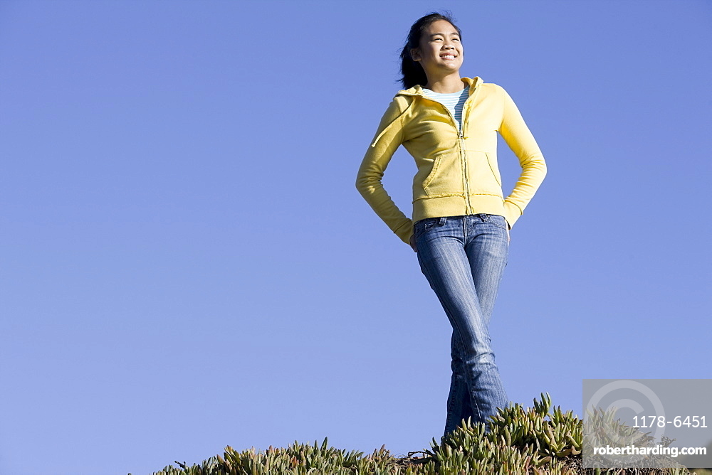 Teenage girl standing on hill