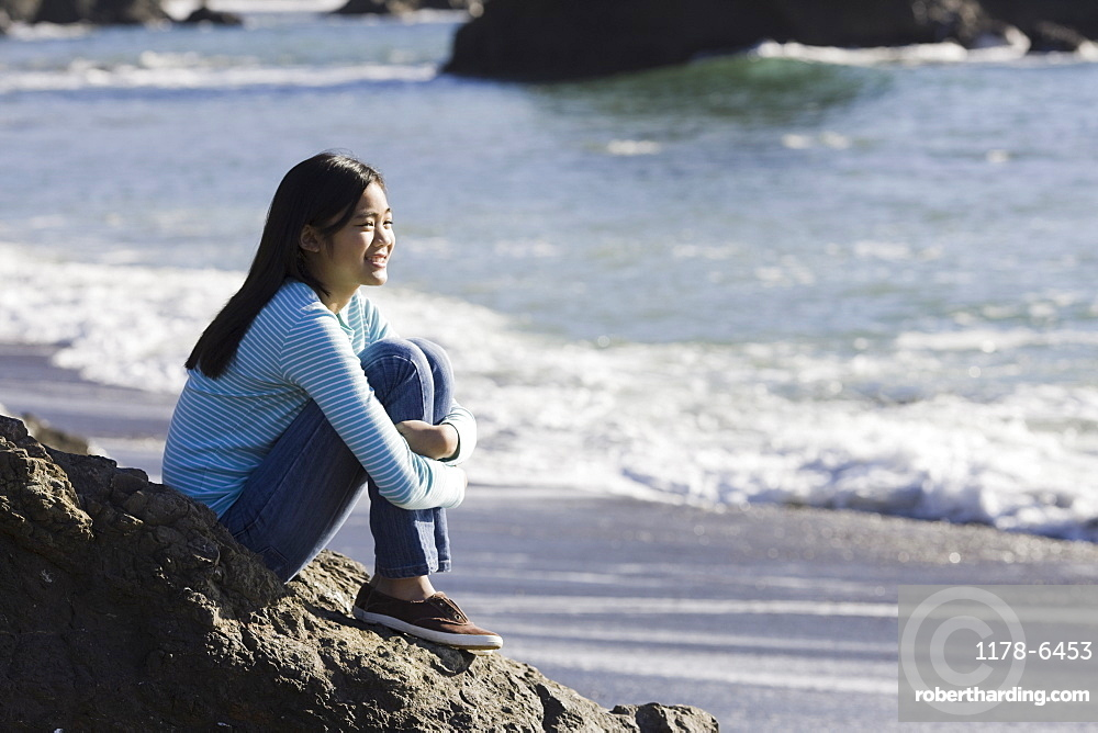 Teenage girl sitting on coastal rock