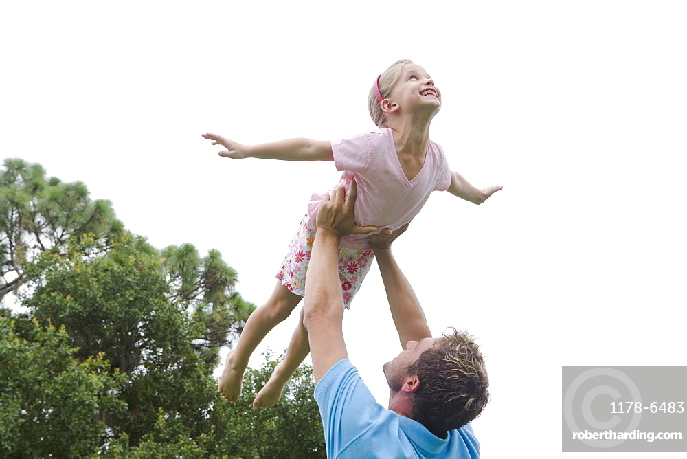Father lifting daughter in backyard