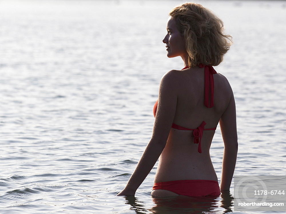 Beautiful woman standing in lake at sunrise