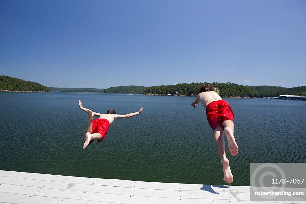 USA, Arkansas, Murfreesboro, Two brothers (8-9, 12-13) jumping into water, USA, Arkansas, Murfreesboro
