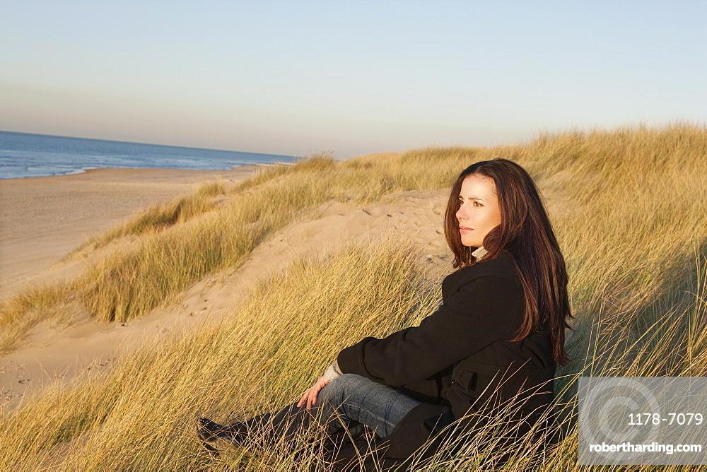 Netherlands, Zeeland, Haamstede, Woman relaxing on sand dune, Netherlands, Zeeland, Haamstede