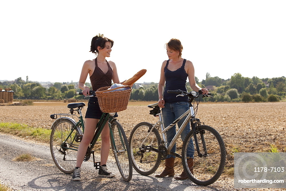 France, Picardie, Albert, Young women on bikes on country road, France, Picardie, Albert