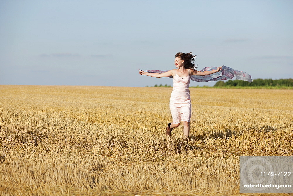 France, Picardie, Albert, Young woman running through stubble with shawl, France, Picardie, Albert