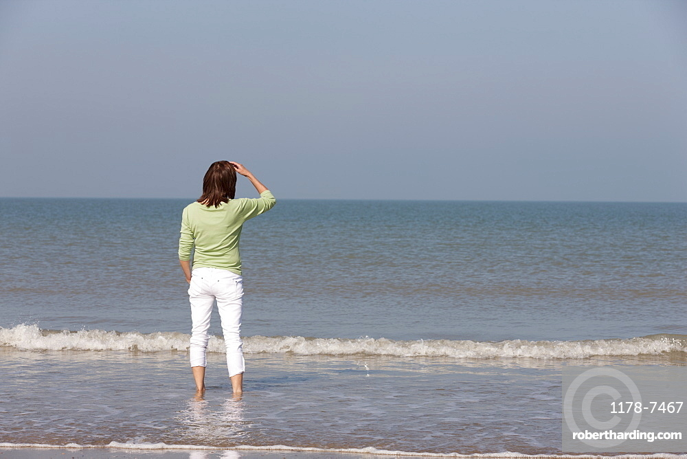 Woman on beach looking out to sea