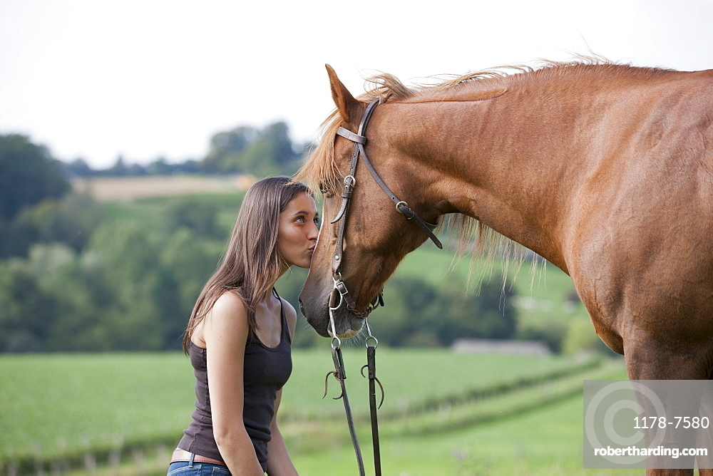 Young woman kissing horse in field