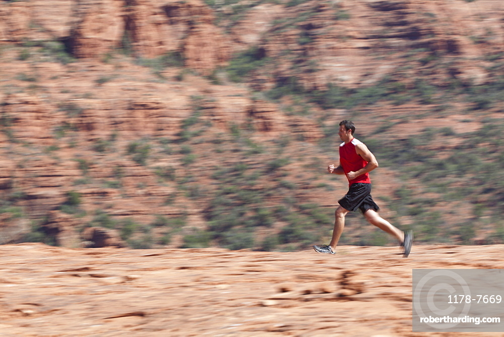 USA, Arizona, Sedona, Young man running in desert