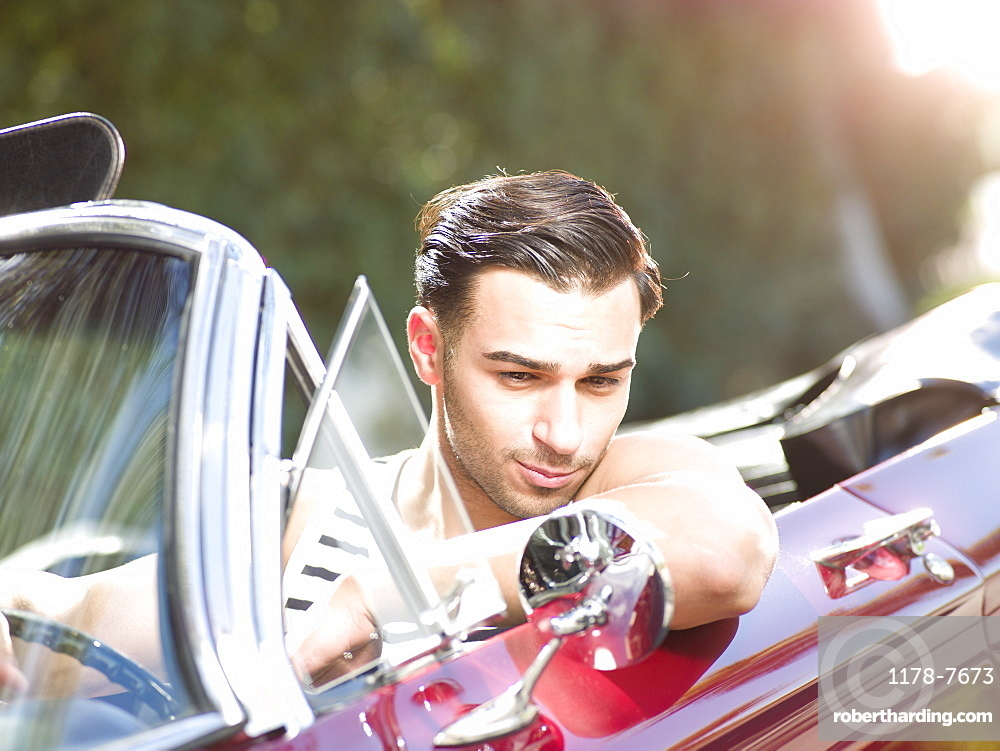 Smiling young man in convertible car