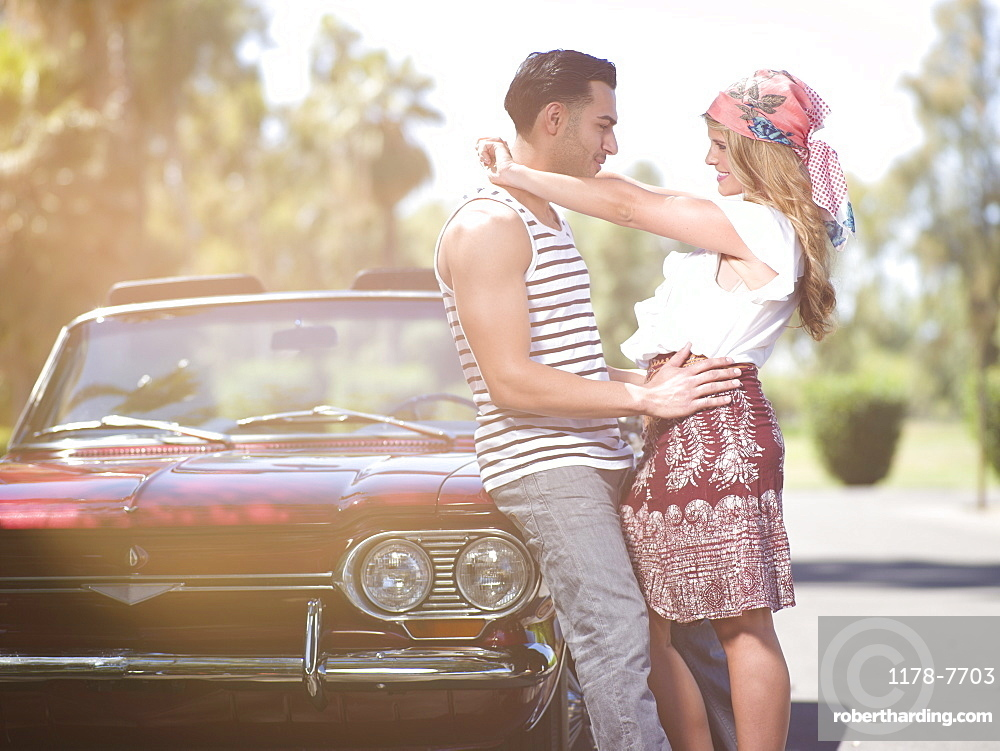 Couple embracing near convertible car