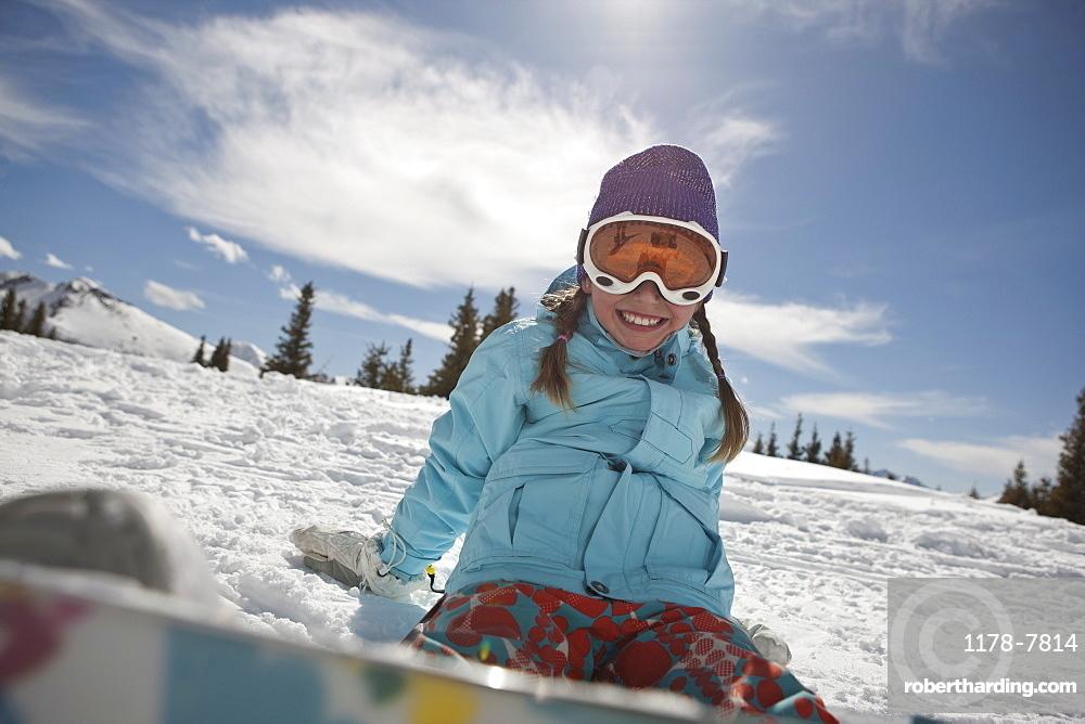 USA, Colorado, Telluride, Girl (10-11) posing with snowboard in winter scenery