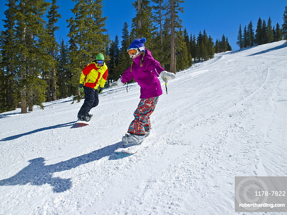 USA, Colorado, Telluride, Father and daughter (10-11) snowboarding