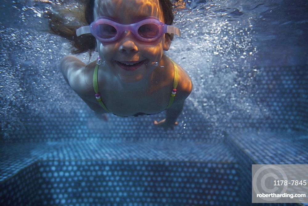 Portrait of girl (4-5) swimming underwater