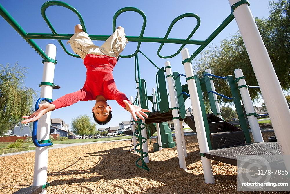 USA, California, Boy (12-13) climbing at playground