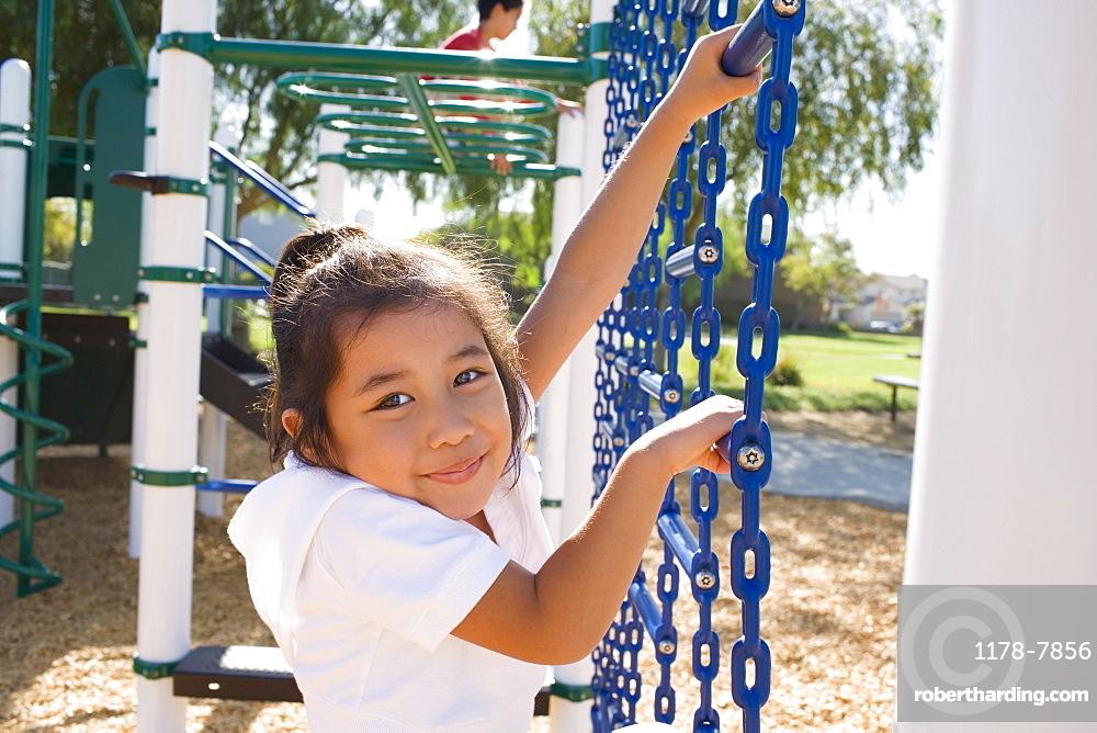 USA, California, Portrait of girl (4-5) climbing at playground