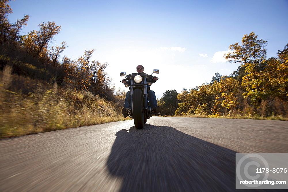 USA, Colorado, Carbondale, Mature man driving motorcycle