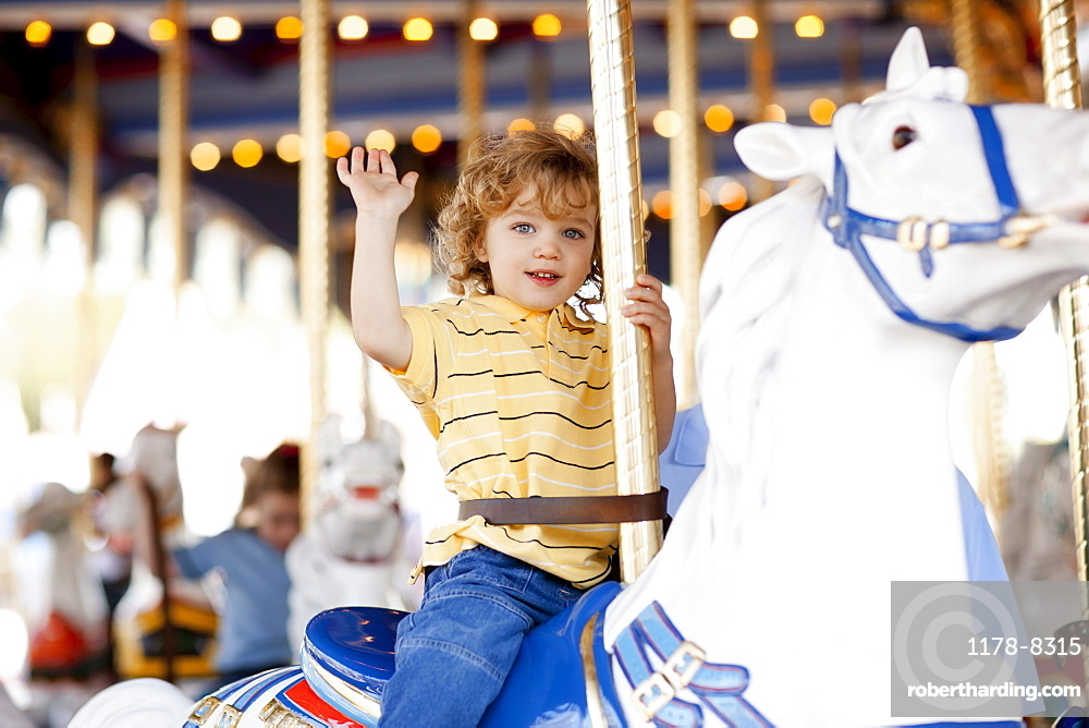 USA, California, Los Angeles, Boy (4-5) sitting on carousel's horse and waving