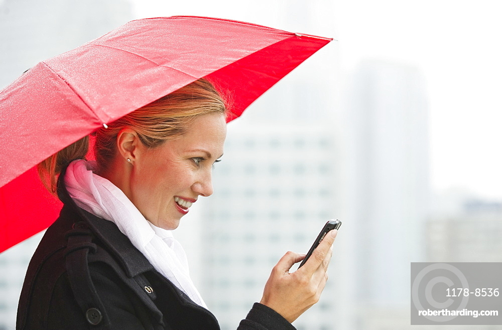 Woman texting on a rainy day