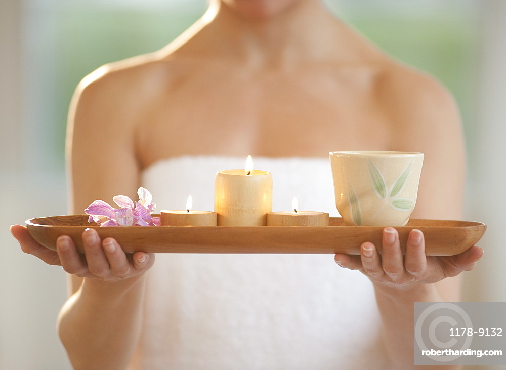 Mid-adult woman wearing towel carrying candles on tray