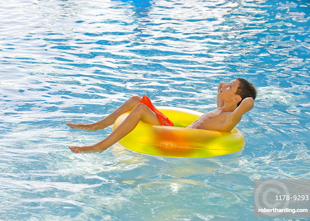 Boy relaxing in inflatable tube in swimming pool