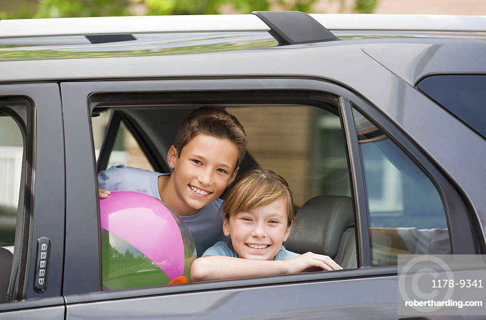 Brother and sister looking out car window
