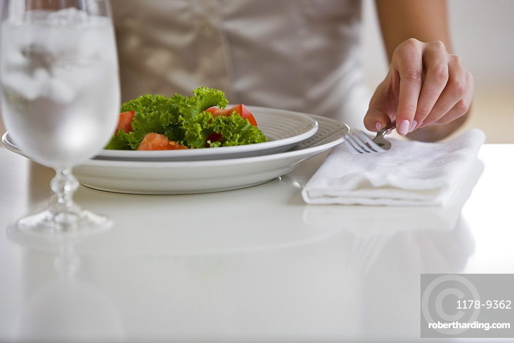 Woman lifting fork next to plate of food