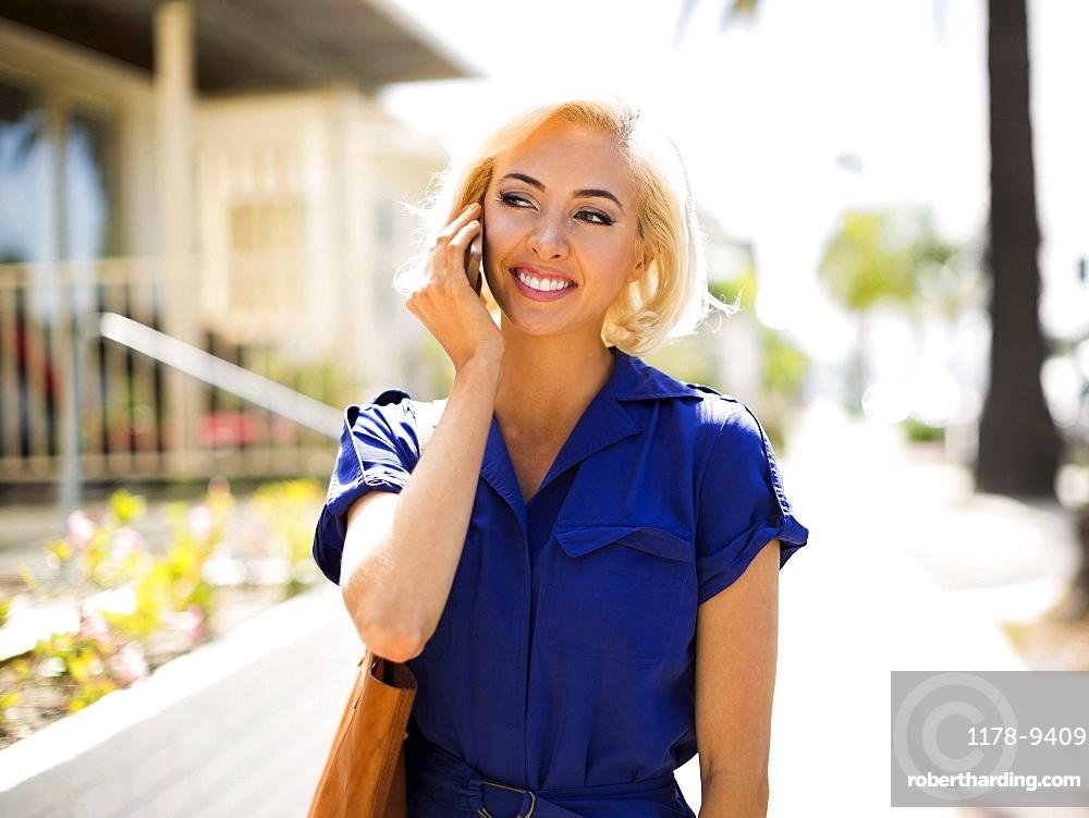 Woman using phone and walking street, Costa Mesa, California