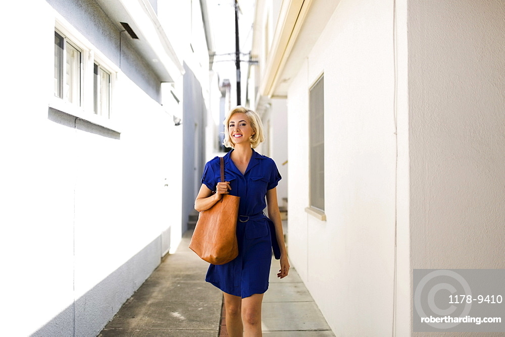 Front view of women in blue dress walking between white buildings