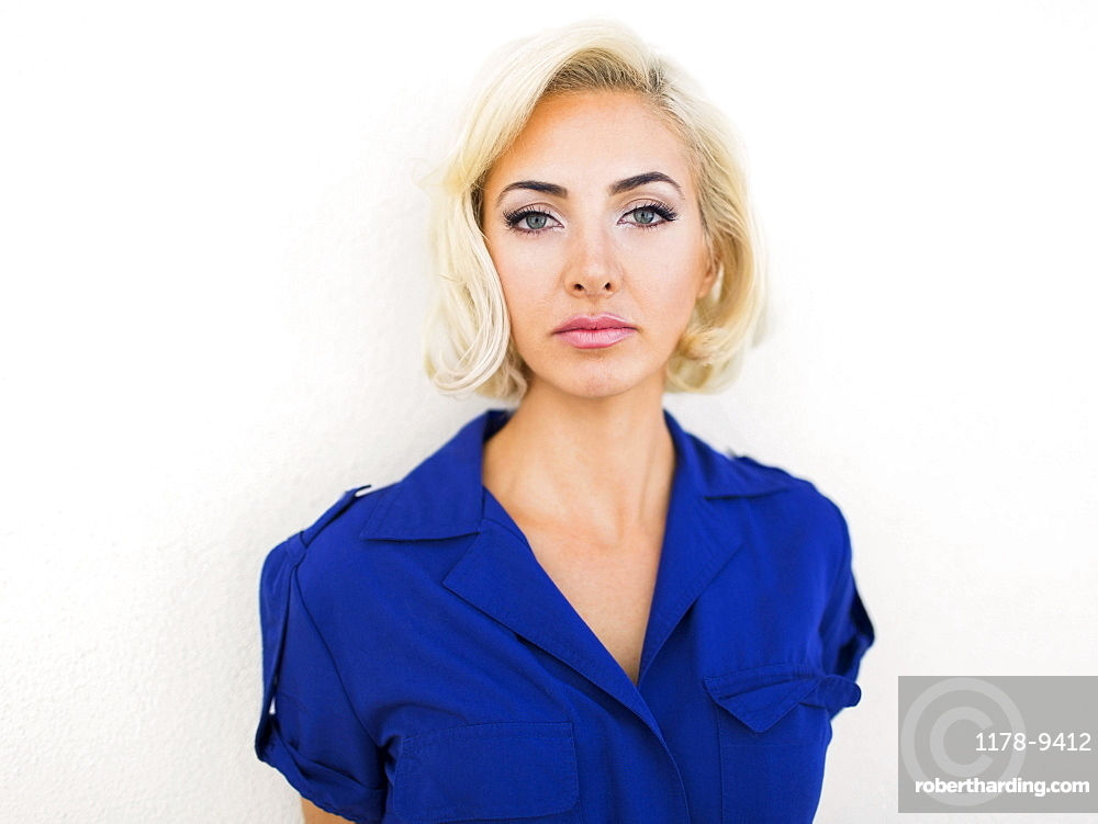 Woman in blue dress posing to camera against white background
