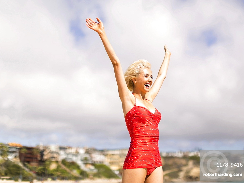 Woman wearing red one piece swimsuit standing on beach with arms raised, Costa Mesa, California