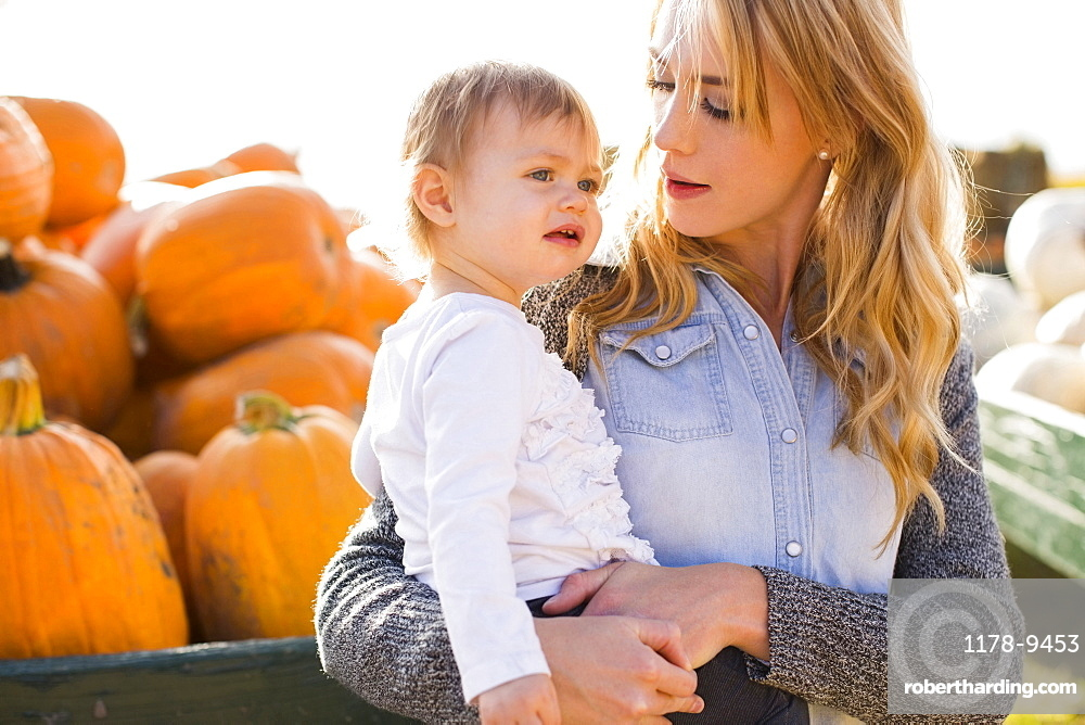 Mother and daughter (12-17 months) with pumpkins in background