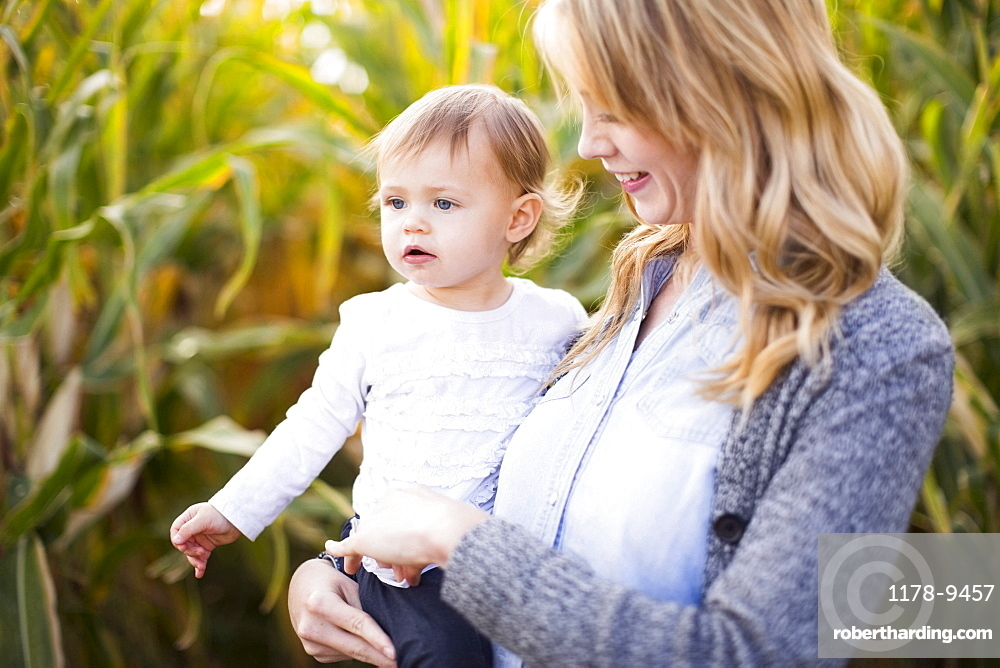 Mother and daughter (12-17 months) in corn field