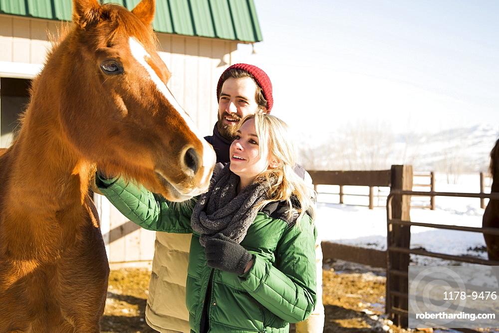 Young couple stroking horse, Salt Lake City, Utah