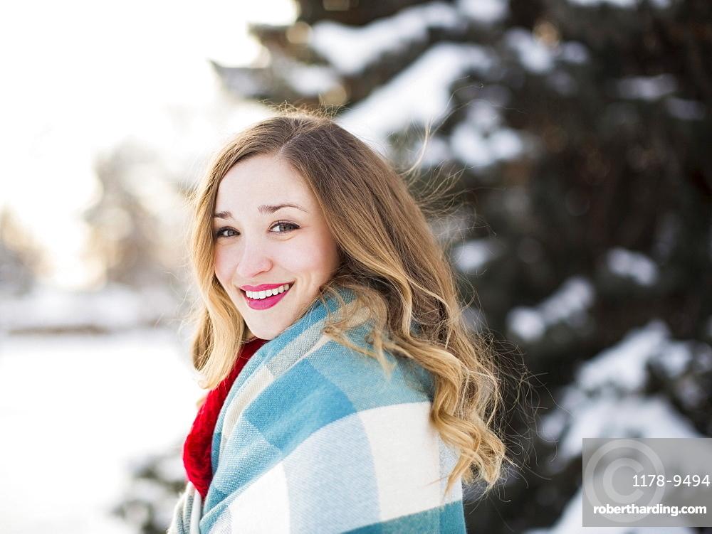 Portrait of woman wrapped in blanket smiling outdoors, Salt Lake City, Utah