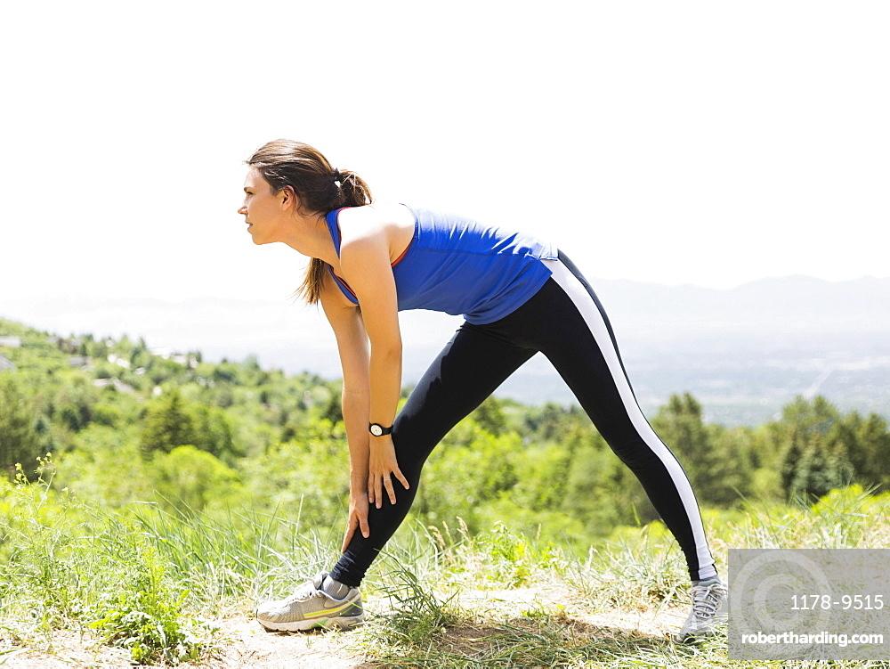 Female jogger stretching, USA, Utah, Salt Lake City