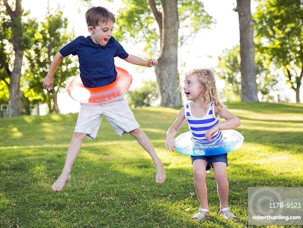 Two kids (4-5, 6-7) playing with inflatable rings in park, USA, Utah, Salt Lake City