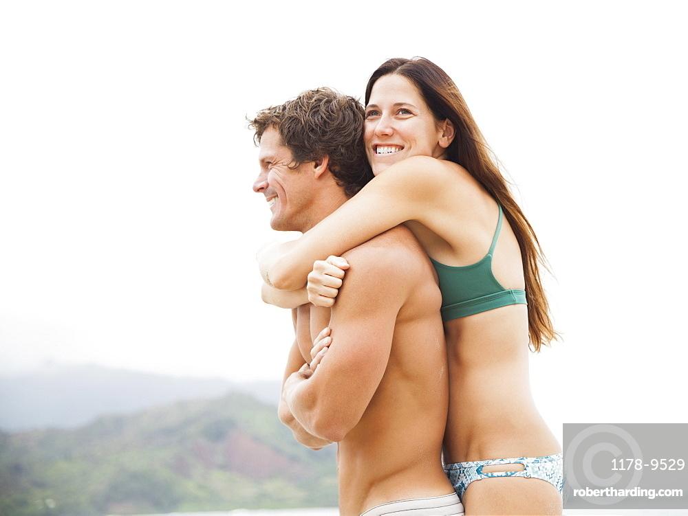 Couple embracing on beach, Kauai, Hawaii