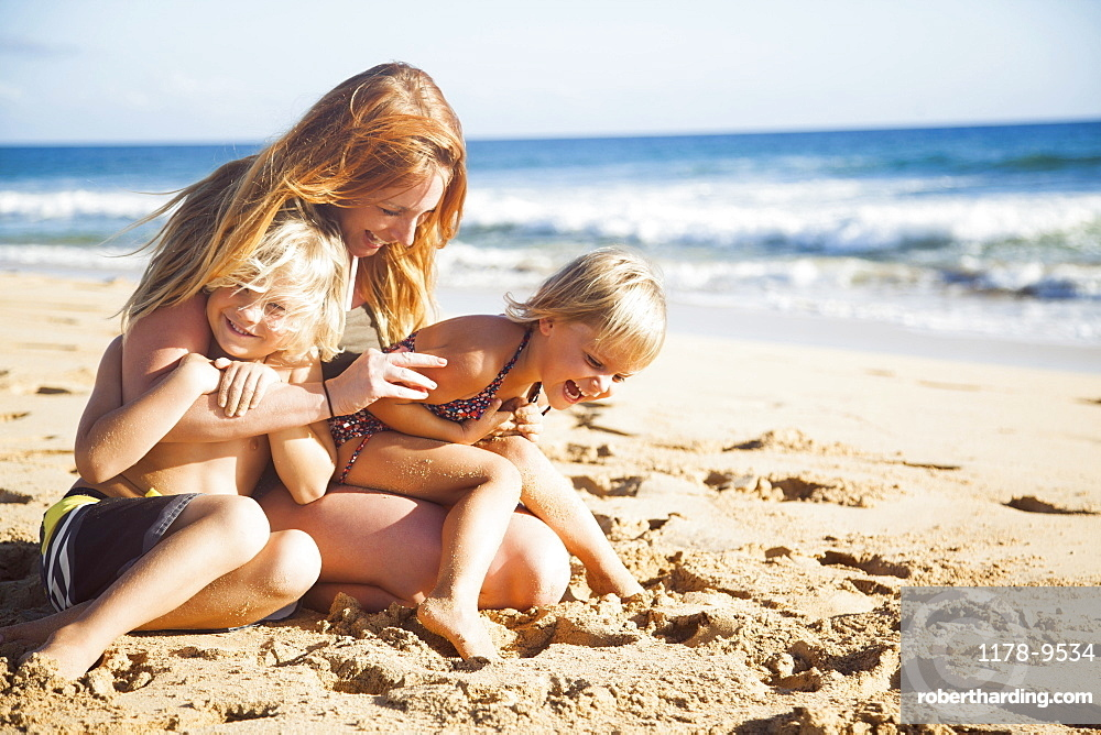 Mother with son (6-7) and daughter (2-3) on beach, Kauai, Hawaii